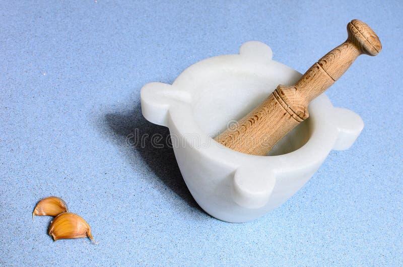 Пестик домодельного мрамора над голубым столом silestone с чесноком стоковые изображения