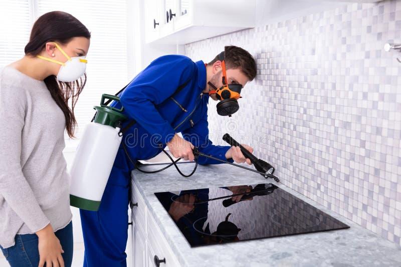Пестицид работника распыляя около плиты индукции стоковая фотография