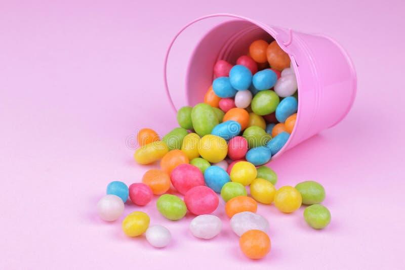 Пестротканая круглая конфета в розовом декоративном ведре на розовой предпосылке стоковое изображение rf
