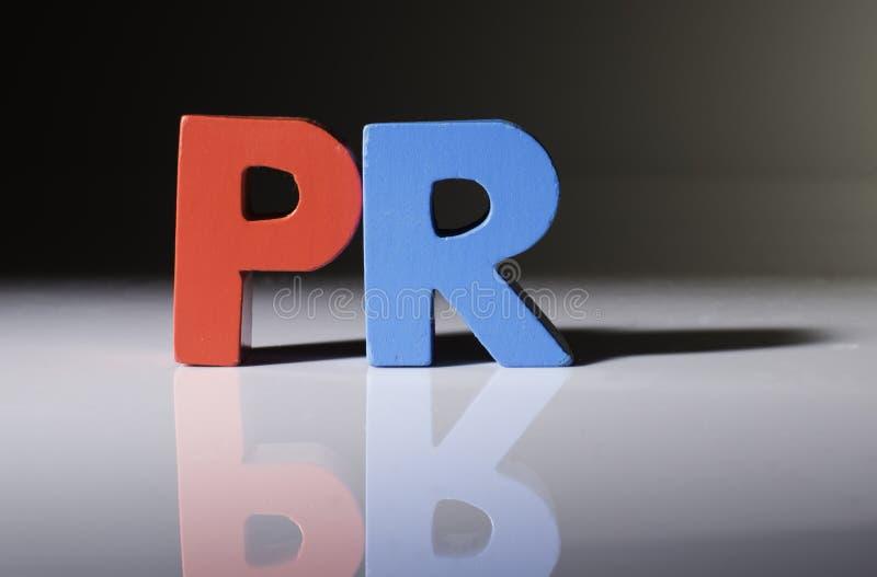 Пестротканое слово PR сделанное из древесины. стоковые фото