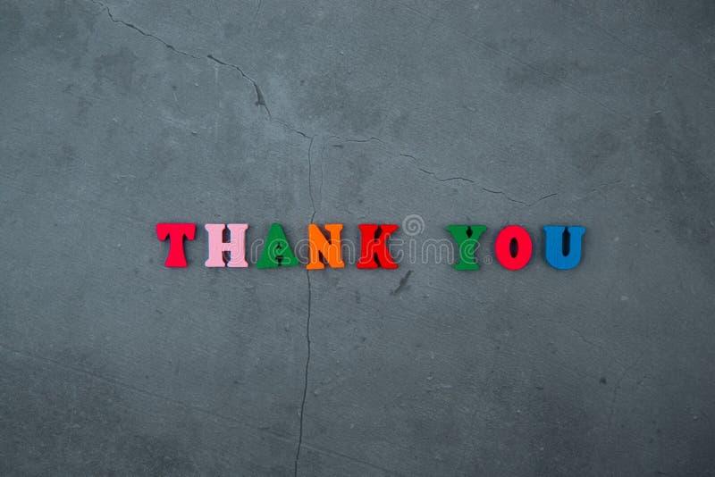 Пестротканые благодарят вас слово сделано деревянных писем на серой заштукатуренной предпосылке стены стоковые фото