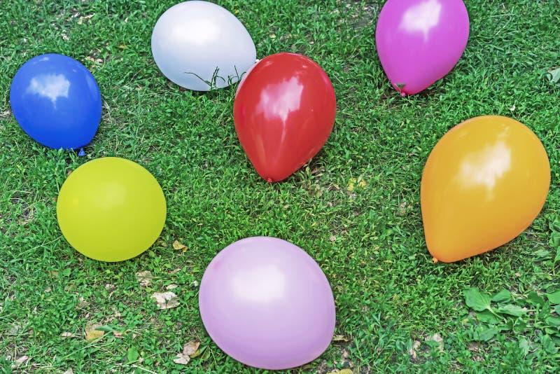 Пестротканые воздушные шары на зеленой траве Предпосылка покрашенных воздушных шаров стоковая фотография