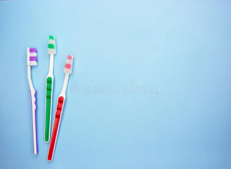 Пестротканые зубные щетки на голубой предпосылке с космосом экземпляра стоковые изображения