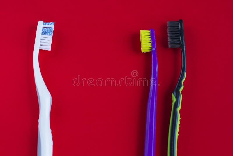 Пестротканые зубные щетки на красной предпосылке стоковые изображения rf
