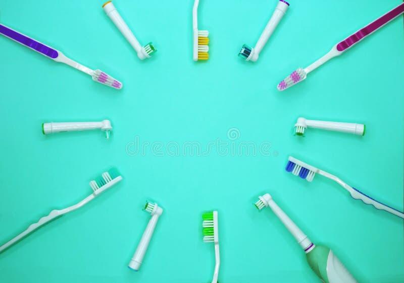 Пестротканые зубные щетки на предпосылке бирюзы с космосом экземпляра стоковая фотография rf