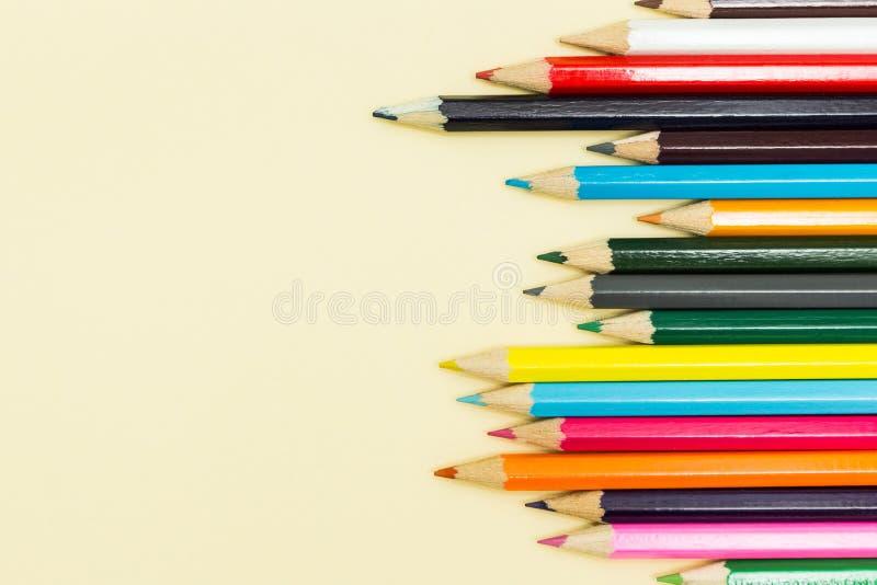Пестротканые карандаши на пастельной желтой предпосылке, космосе для  стоковое изображение rf