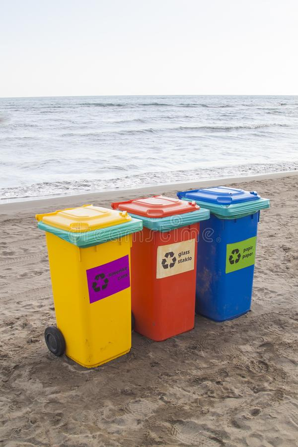 пестротканые контейнеры для сортировать отброс на пляж ag стоковая фотография