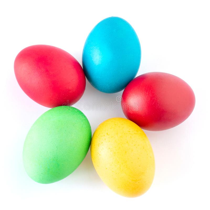 Пестротканые пасхальные яйца лежат на белой предпосылке Желтое, красное, зеленое и голубое яйцо сложенное в форме цветка стоковая фотография