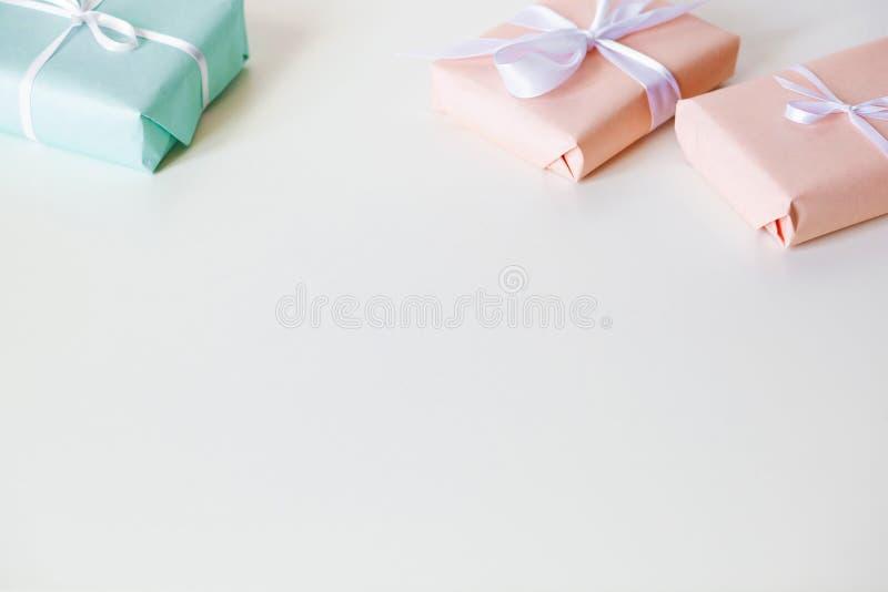 Пестротканые подарочные коробки на белом столе r r стоковые фотографии rf