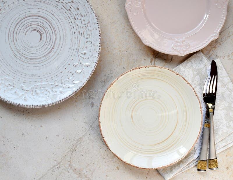 Пестротканые пустые керамические плиты на мраморной предпосылке Поставьте установку на обсуждение Затрапезный шик или ретро стиль стоковая фотография rf