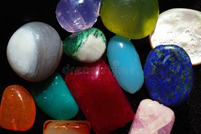 Пестротканые самоцветные камни на черном конце-вверх стоковое фото rf