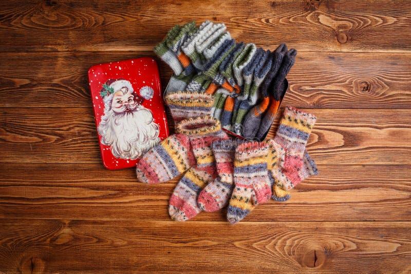 Пестротканые связанные носки младенца и коробка металла с изображением Санта Клауса на деревянной предпосылке стоковые фото
