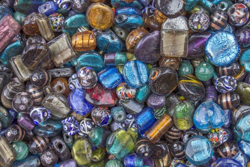 Пестротканые стеклянные самоцветы с отверстиями лежат в куче стоковое изображение rf