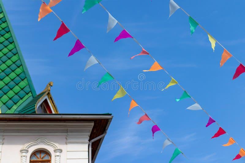 Пестротканые флаги на предпосылке неба лента с флагами красных, желтых, фиолетовых, оранжевых и голубых цветов стоковая фотография