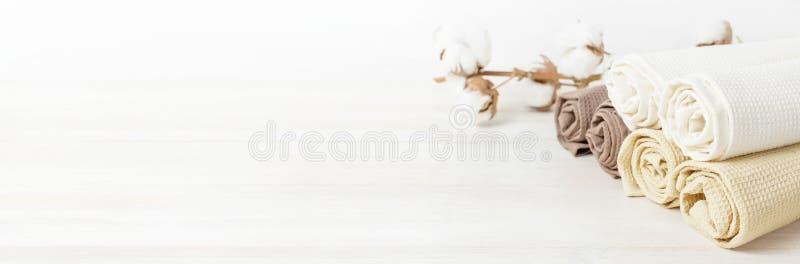 Пестротканые чистые полотенца с ветвью хлопка на светлой деревянной предпосылке с космосом экземпляра Текстура хлопка, полотенца  стоковые изображения rf