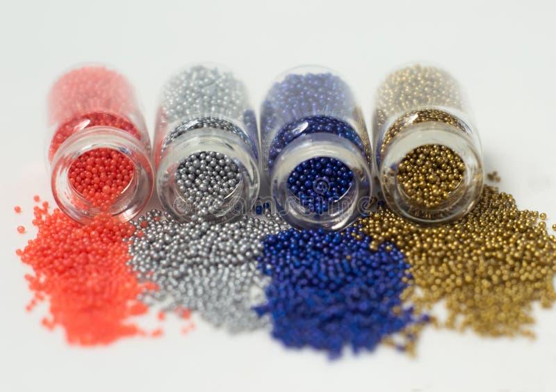 Пестротканые шарики в стеклянных опарниках Шарики политы на белой предпосылке Пластиковые пестротканые полимеры Пластиковые pille стоковые изображения rf