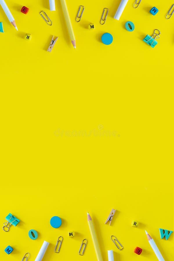 Пестротканые школьные принадлежности на желтой предпосылке с космосом экземпляра Вертикальное плоское положение для социальных ра стоковая фотография rf