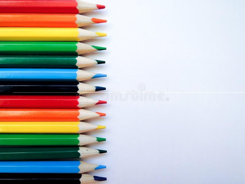Пестротканые яркие карандаши лож одинакового размера плоской на белой бумаге, отделенные цветами радуги стоковое изображение