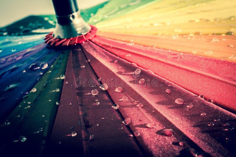 Пестротканый красочный зонтик с всеми цветами радуги с дождевыми каплями стоковое изображение rf
