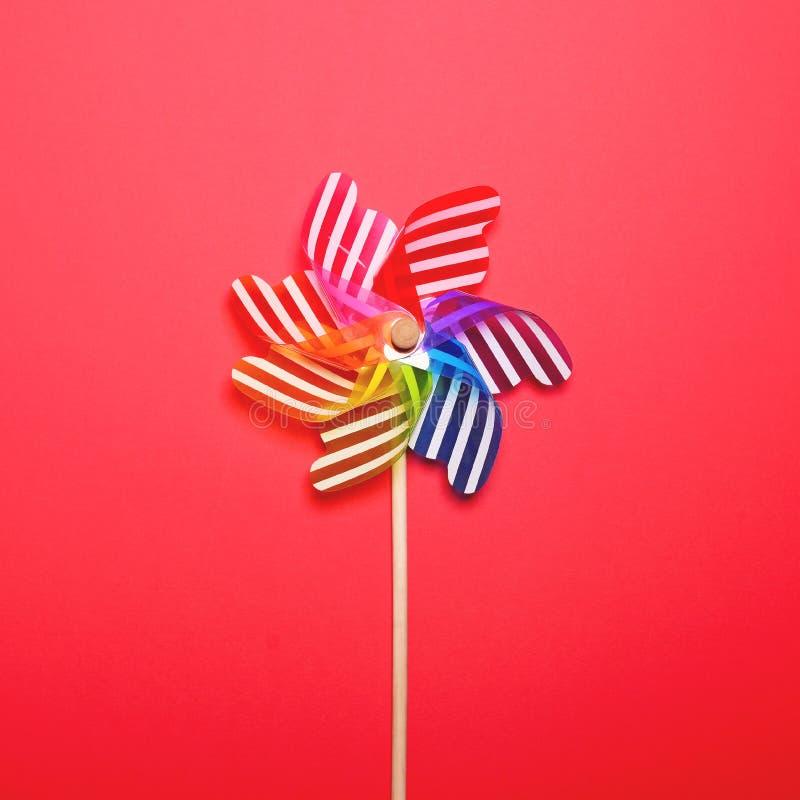 Пестротканый pinwheel против красной предпосылки - минимального плоского положенного дизайна стоковое изображение rf