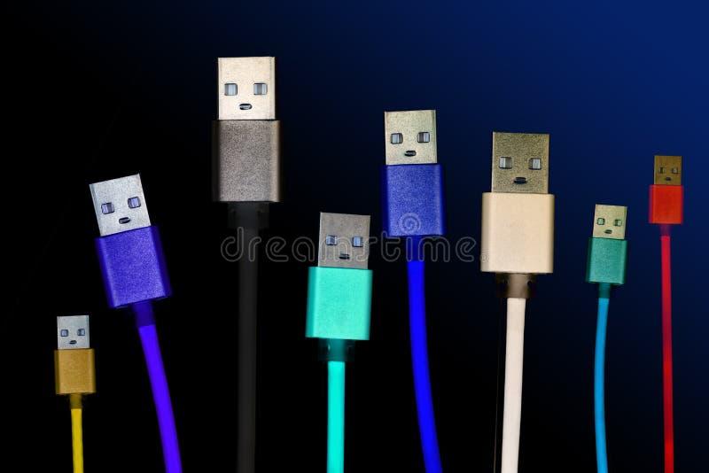 8 пестротканых кабелей usb устроены вертикально, на темной, хмурой изолированной предпосылке Семья соединяет будущее technologie стоковое фото rf