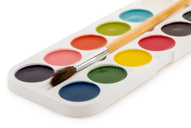 Пестрые краски кладут в коробку с щеткой стоковая фотография rf