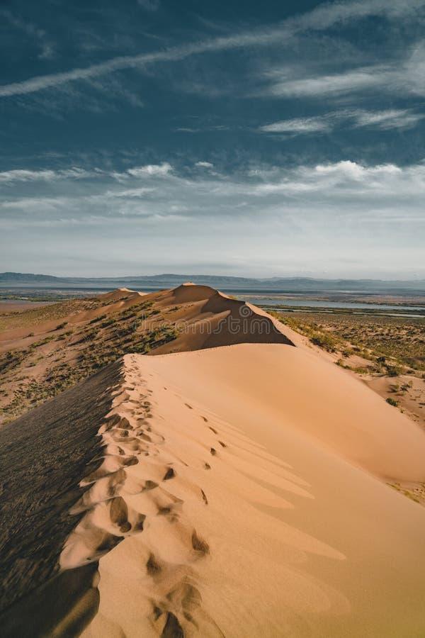 Песчанные дюны под голубым небом Пустыня Сахары, ранее, дома в деревне возвратила должное к движению песков стоковое изображение