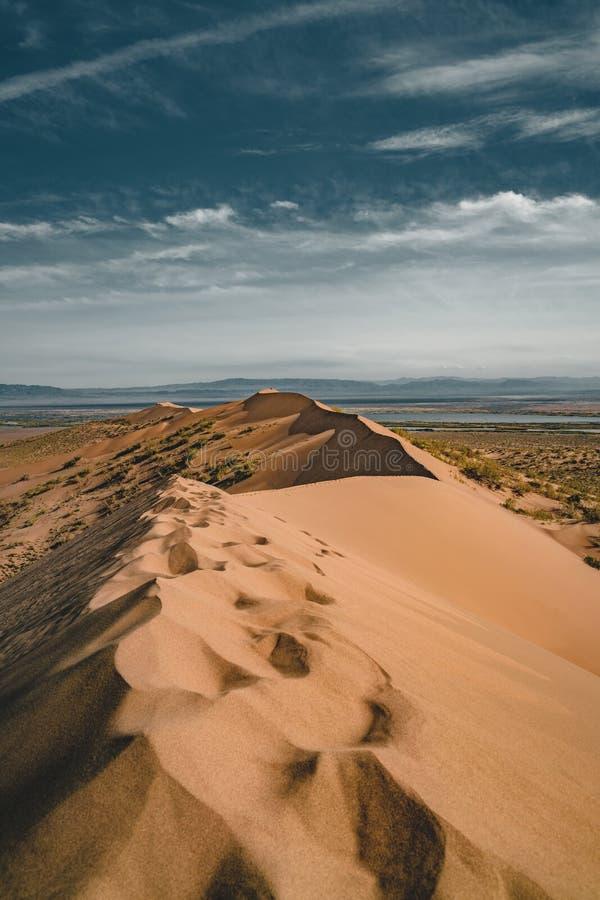Песчанные дюны под голубым небом Пустыня Сахары, ранее, дома в деревне возвратила должное к движению песков стоковая фотография