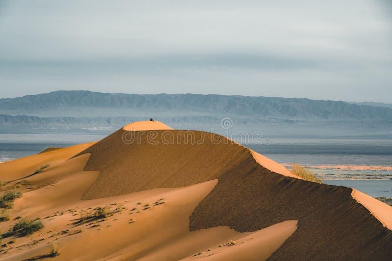 Песчанные дюны под голубым небом Пустыня Сахары, ранее, дома в деревне возвратила должное к движению песков стоковое фото