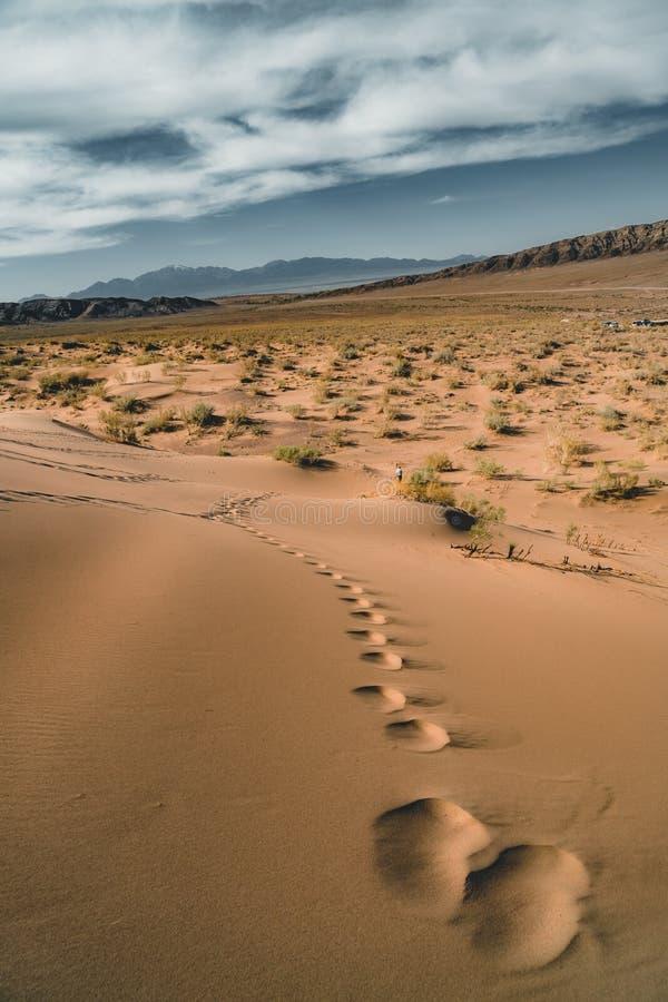 Песчанные дюны под голубым небом Пустыня Сахары, ранее, дома в деревне возвратила должное к движению песков стоковые фото