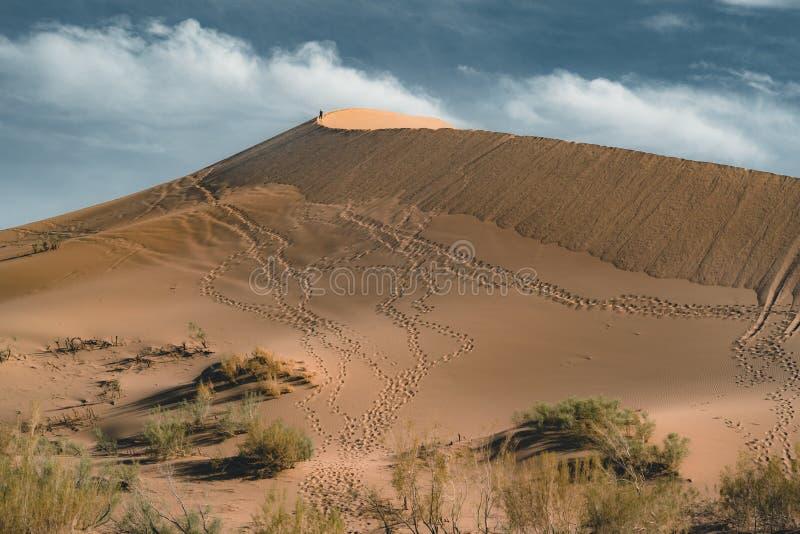 Песчанные дюны под голубым небом Пустыня Сахары, ранее, дома в деревне возвратила должное к движению песков стоковые изображения rf