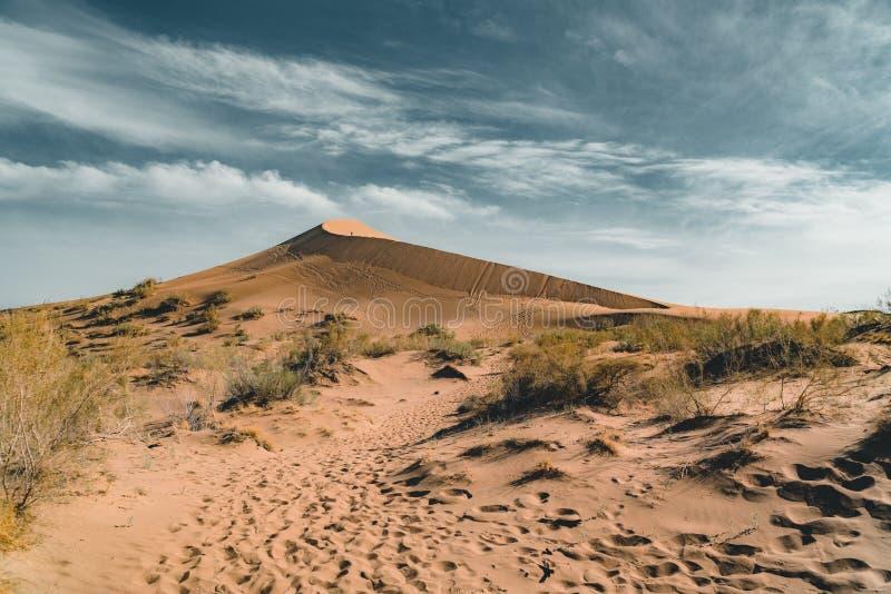 Песчанные дюны под голубым небом Пустыня Сахары, ранее, дома в деревне возвратила должное к движению песков стоковое фото rf