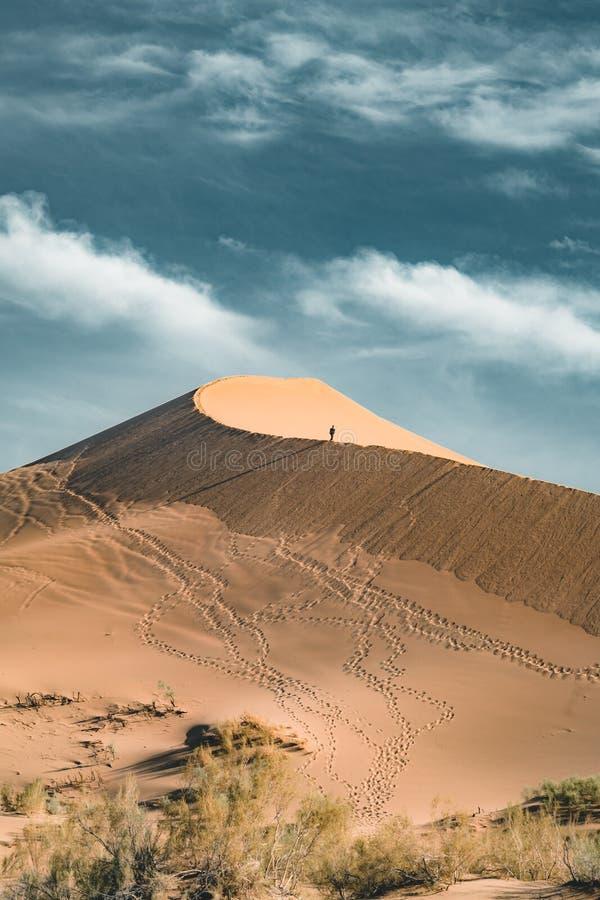 Песчанные дюны под голубым небом Пустыня Сахары, ранее, дома в деревне возвратила должное к движению песков стоковые фотографии rf