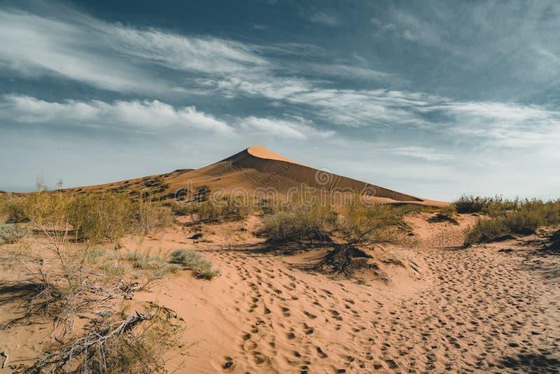 Песчанные дюны под голубым небом Пустыня Сахары, ранее, дома в деревне возвратила должное к движению песков стоковое изображение rf