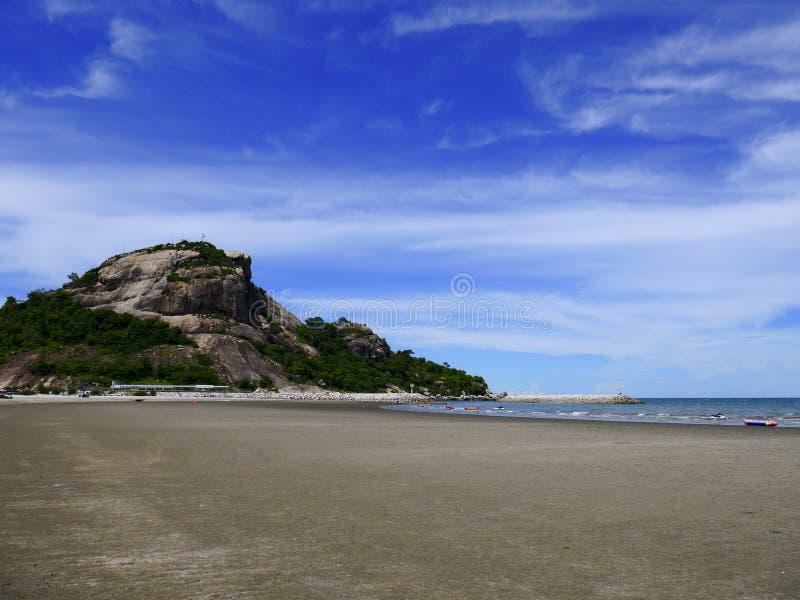 Песчаные пляжи с скалистыми горами и предпосылкой голубого неба стоковые фотографии rf