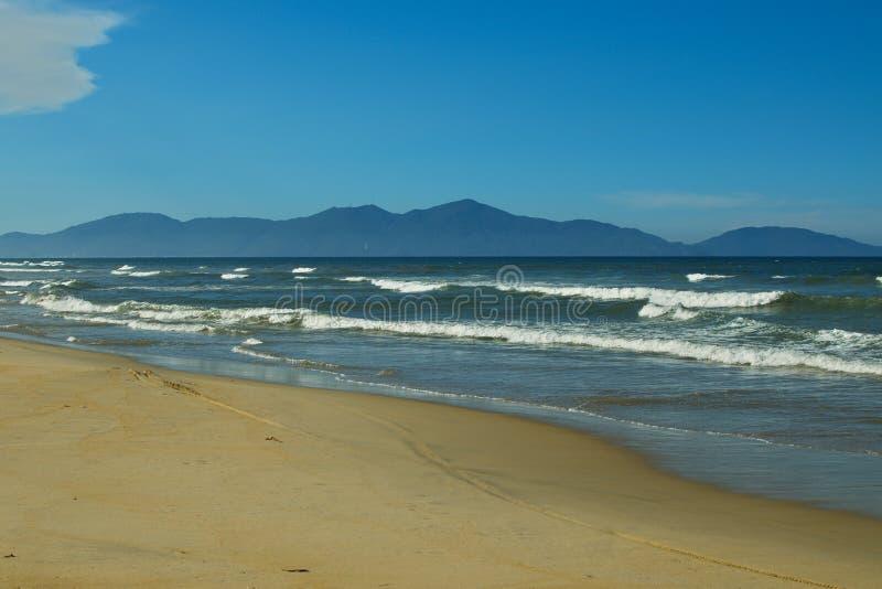 Песчаный пляж, голубое море с пеной белого моря и горы на предпосылке голубого неба стоковое изображение rf