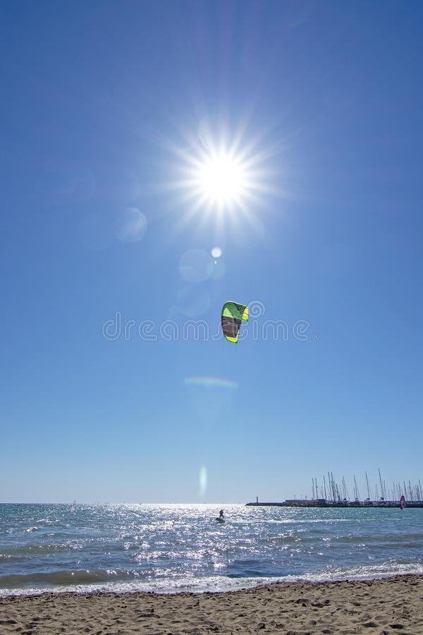 Песчаный пляж и летание kitesurfer высокое против голубого неба с солнцем и пирофакелами звезды форменными стоковые изображения