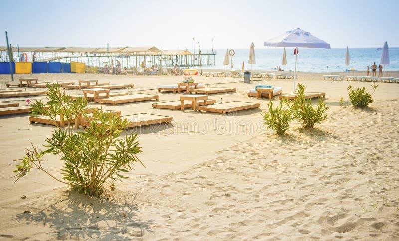 Песчаный пляж на голубой предпосылке моря Зонтики и шезлонги на береге моря Летний день на концепции каникул остатков пляжа стоковые фотографии rf