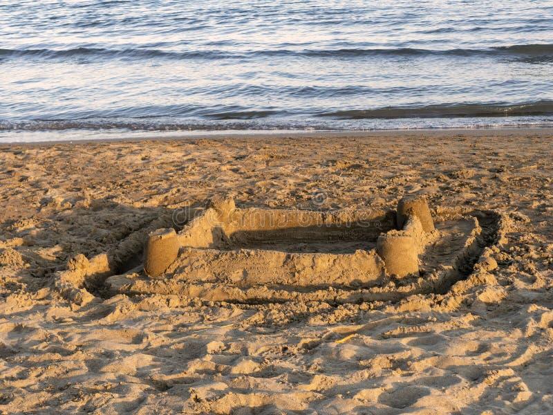 Песчаный пляж с получившимся отказ sandcastle и воды окаймляются, море Заход солнца Warmm стоковые изображения