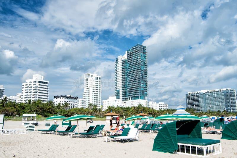 Песчаный пляж при люди ослабляя на стульях под зелеными зонтиками стоковая фотография