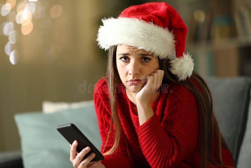 Печальная женщина, которая держит телефон дома на Рождество стоковые изображения rf