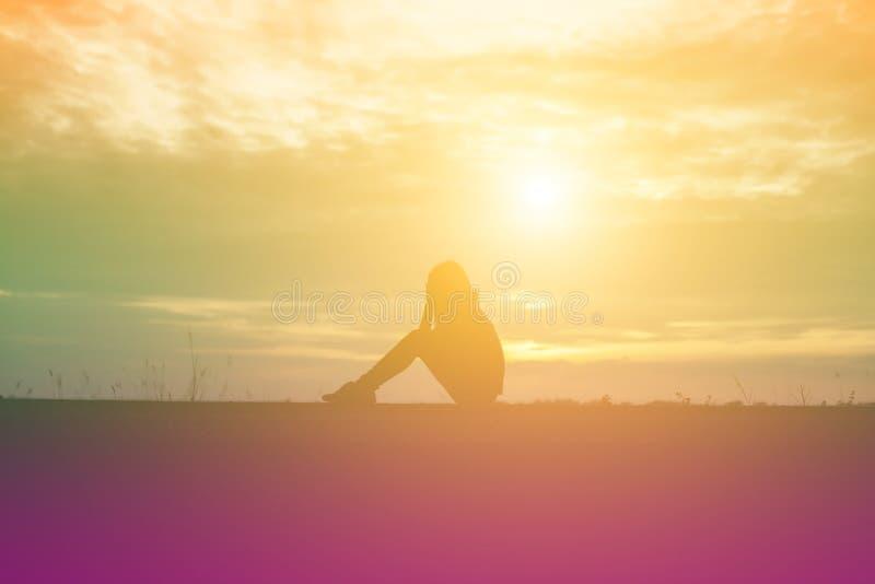 Печальная и подавленная женщина сидит одна стоковые фото