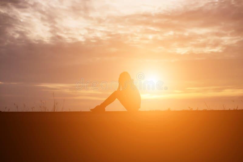 Печальная и подавленная женщина сидит одна стоковые изображения