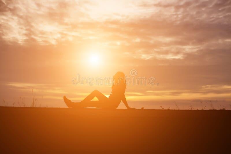 Печальная и подавленная женщина сидит одна стоковая фотография rf