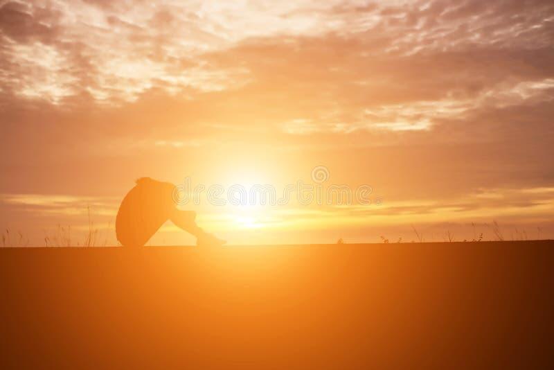 Печальная и подавленная женщина сидит одна стоковое фото rf