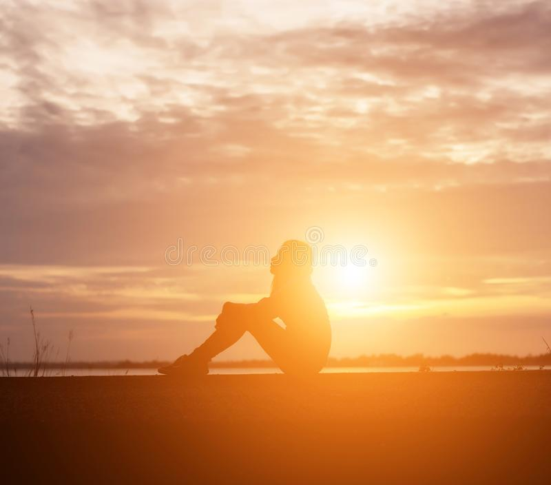 Печальная и подавленная женщина сидит одна стоковые фотографии rf