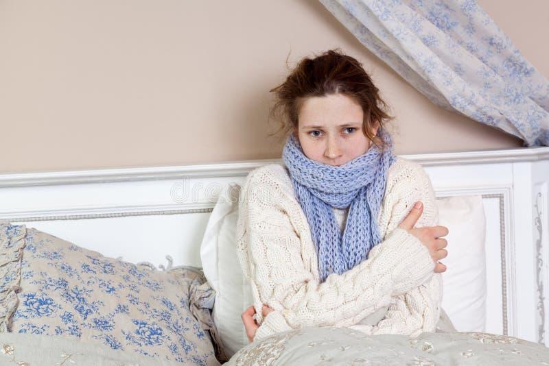 Печальная одинокая молодая женщина в белом свитере и синем шарфе, почуРстоковое изображение rf
