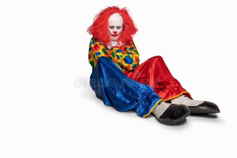 Печальный клоун, сидящий на полу на изолированном фоне стоковое фото