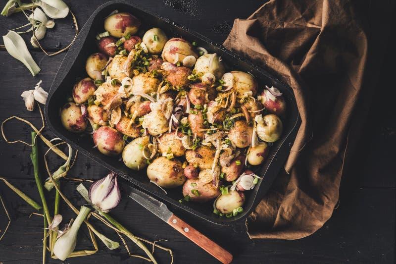 Печеные картофели с луками, чесноком и специями на темной деревенской предпосылке r стоковое фото rf