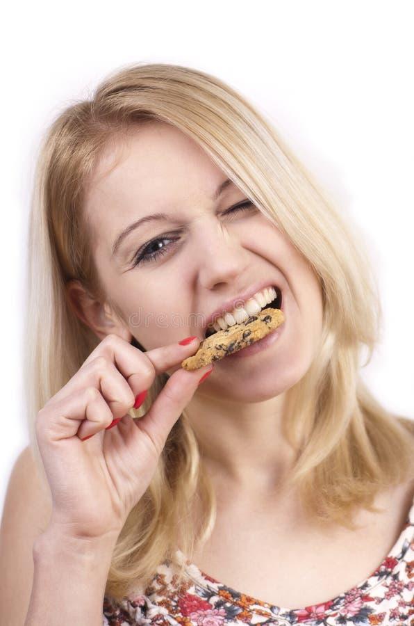 печенье есть детенышей женщины гримасы стоковое изображение